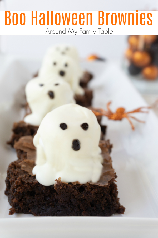 Brownies with ghost marshmallows on white platter