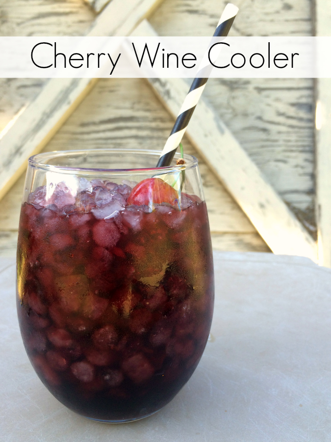 cherry wine cooler in a tall glass with a straw