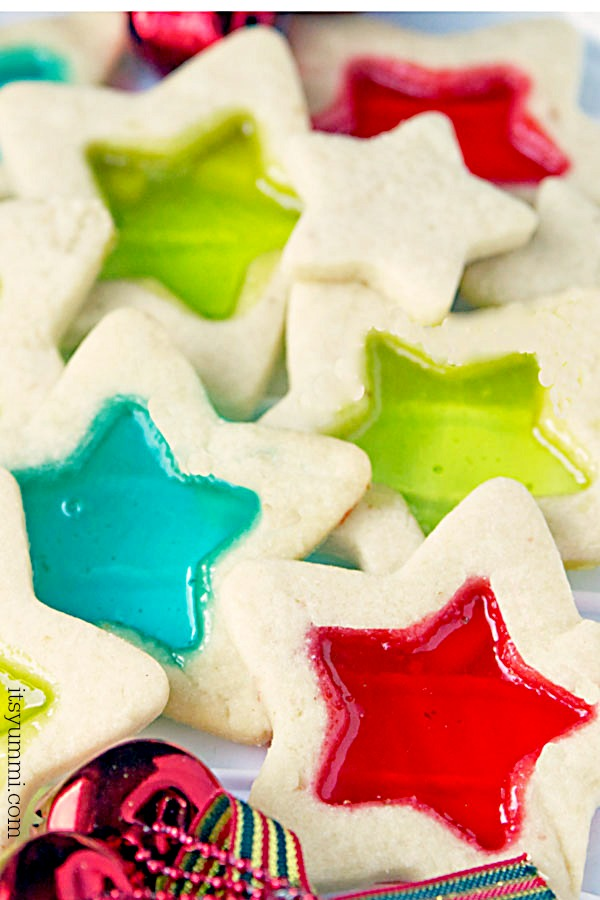 Stained glass cookies are a delicious, beautiful, and easy to make holiday cookie. Soft, buttery cookie dough, rolled out and cut into holiday shapes, then filled with melted candies so they look like stained glass.