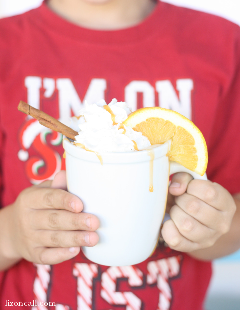 boy holding a white mug of holiday party punch, garnished with whipped cream, an orange slice, and cinnamon stick