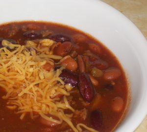 bowl of slow cooker 10 can chili topped with shredded cheddar cheese