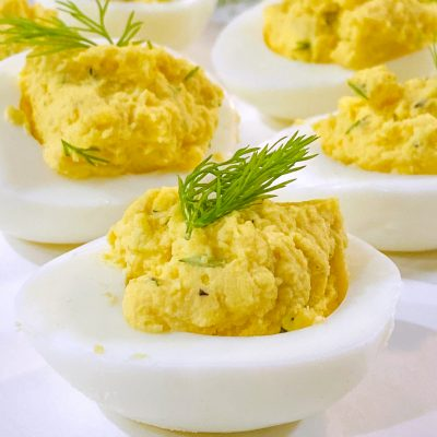 dilled deviled eggs on white plate