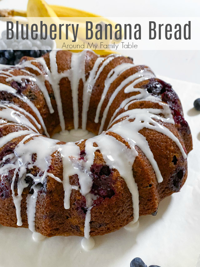 blueberry banana bread on white table with bananas and blueberries