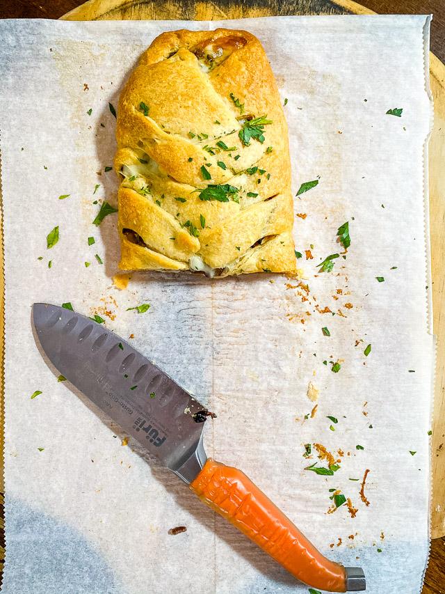 cut Steak & Provolone Crescent Braid on parchment paper on a pizza peel