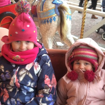 Lily-Belle and Matilda enjoying their time on the carousel at the Helsinki Christmas Market in Senate Square