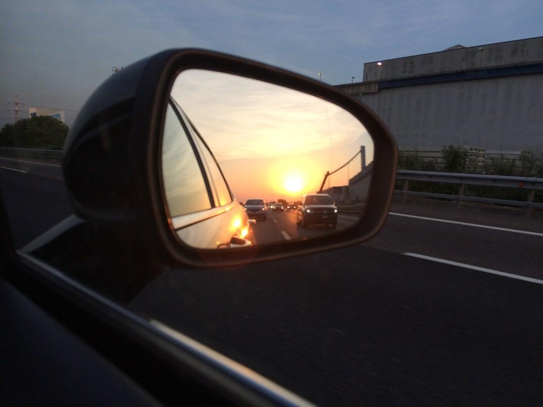 Sunset over Milan viewed through a car wing mirror