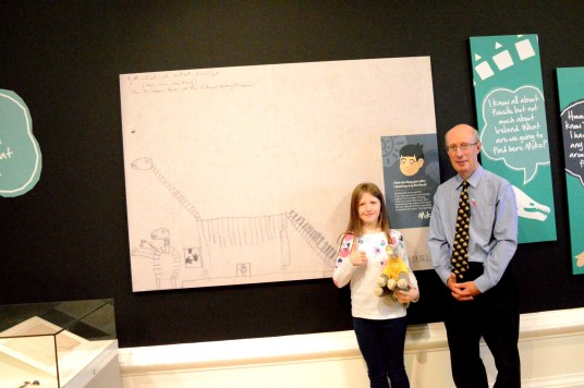 Lily-Belle and Dr Mike Simms beside his 1969 drawing of Dippy the Dinosaur