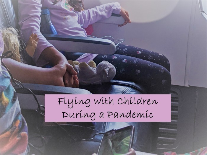 Two children holding hands on an airplane