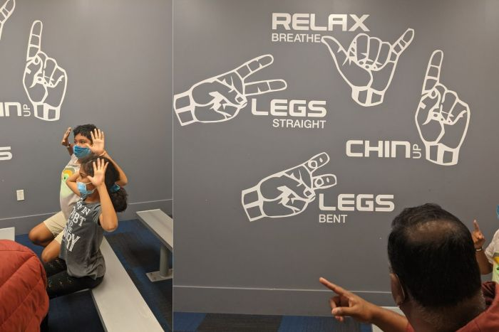 Kids demonstrating the proper hand position for indoor sky diving and a sign showing hand signals for indoor skydiving
