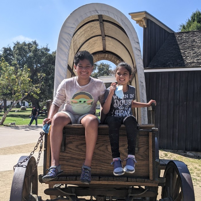 Two children in a covered wagon