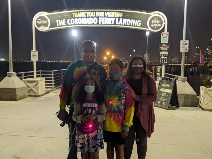 A mother, father, and their two children in front of the Coronado Ferry Landing sign.