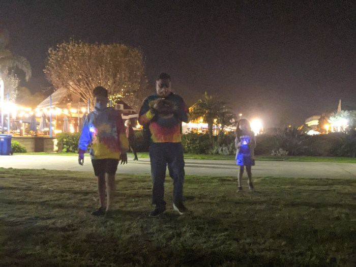 A father and his two children, each wearing glowing necklaces at night