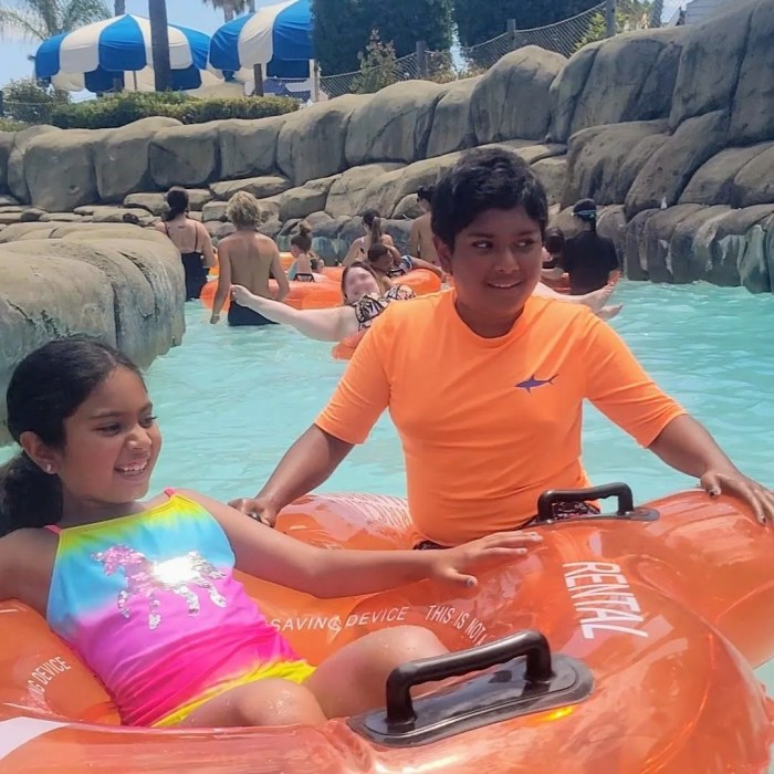 Young boy and young girl float in an orange tube down a lazy river