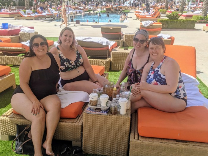 4 women sitting on pool loungers by the pool in Vegas