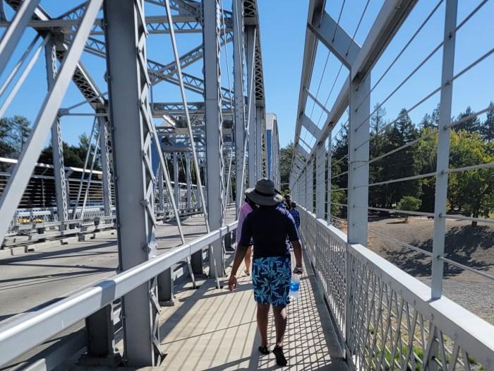 Young man walking across a bridge