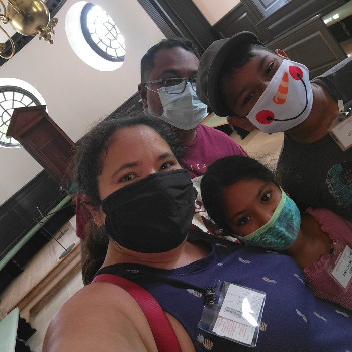 A family of four sitting in a historic building in Colonial Williamsburg, all masked.