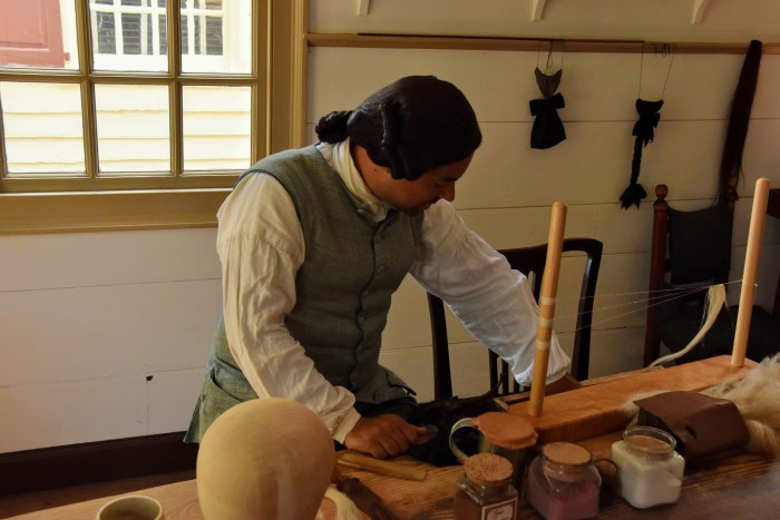 Man dressed in colonial dress with a black wig, showing how he made wigs