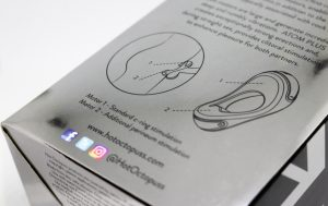 Close up of the box, the box is shiny silver and the image shows an outline of. the Hot Octopuss ATOM Plus and a line diagram of how it's suppose to sit on the penis.