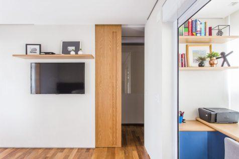 O closet é acessado por uma porta de correr ao lado da TV, aproveitando ao máximo o espaço.