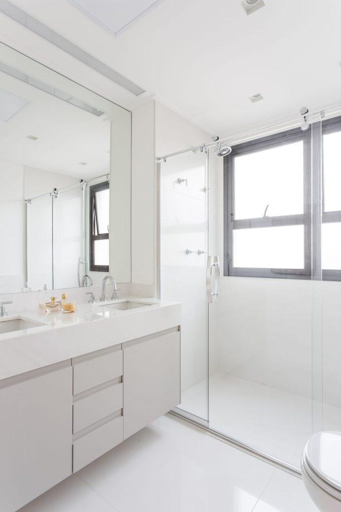 O banheiro da suíte é todo branco com pia dupla.