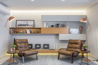 Na composição do espaço de leituras, nichos nos tons cinza e amadeirado recebem objetos decorativos, incluindo quadros apoiados. No clima intimista, a iluminação de LED na parte inferior do mobiliário.