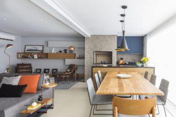 A mesa para as refeições foi transferida para a área gourmet, ampliando o living. No local previsto na planta original, duas poltronas e luminárias de piso deram vida ao cantinho da leitura do casal.