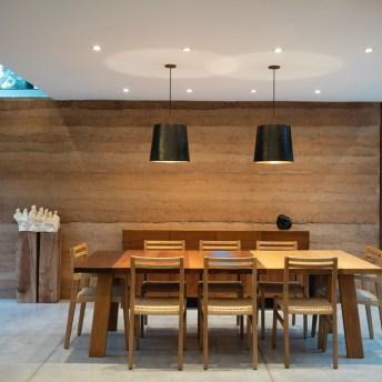 A área de jantar, junto à sala principal, é um ambiente ideal para realizar refeições junto com a família. Ao fundo, destaca-se o volume em taipa onde reside a despensa, lavanderia e banheiro de hospedes.