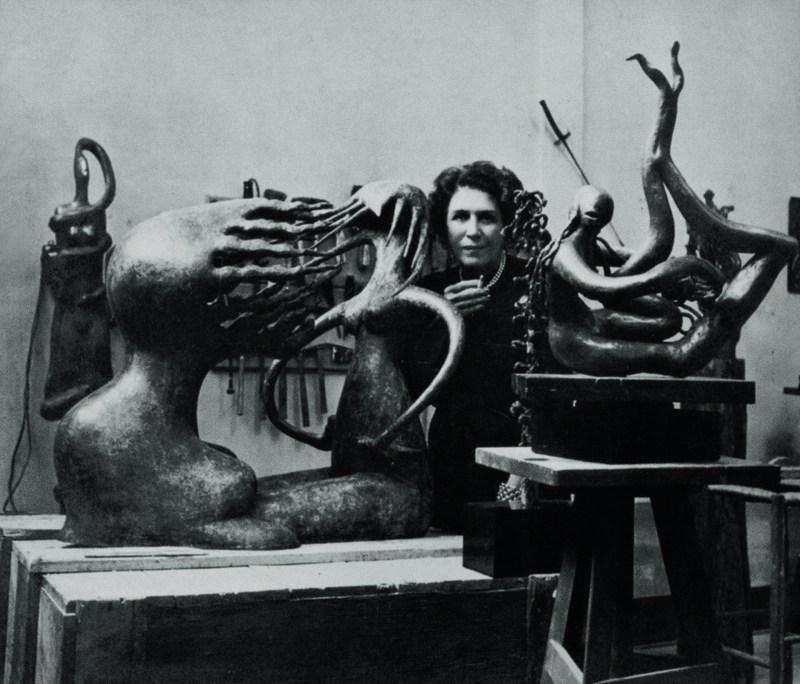 Maria Martins em seu ateliê, entre as esculturas O impossível (1945), Pourquoi toujours [Por que sempre] (1946), Saudade (1945) em primeiro plano e, ao fundo, However [Todavia] (circa 1944) e Apuiseiro (1943), década de 1940_t