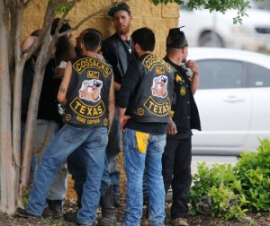 "Bikers congregate against a wall while authorities investigate a Twin Peaks restaurant Sunday, May 17, 2015, in Waco, Texas. Waco Police Sgt. W. Patrick Swanton told KWTX-TV there were ""multiple victims"" after gunfire erupted between rival biker gangs at the restaurant. (Rod Aydelotte/Waco Tribune-Herald via AP)"