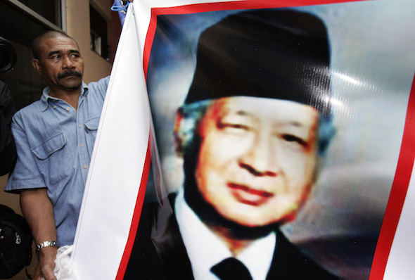 A supporters of Former Indonesian President Suharto holds a banner outside Pertamina hospital in Jakarta to show his support, Saturday, Jan. 12, 2008. Former dictator Suharto was showing slight signs of improvement, doctors said Saturday, hours after he suffered organ failure and was placed on a ventilator with the early, dangerous signs of infection in his lungs. (AP Photo/Vincent Thian)