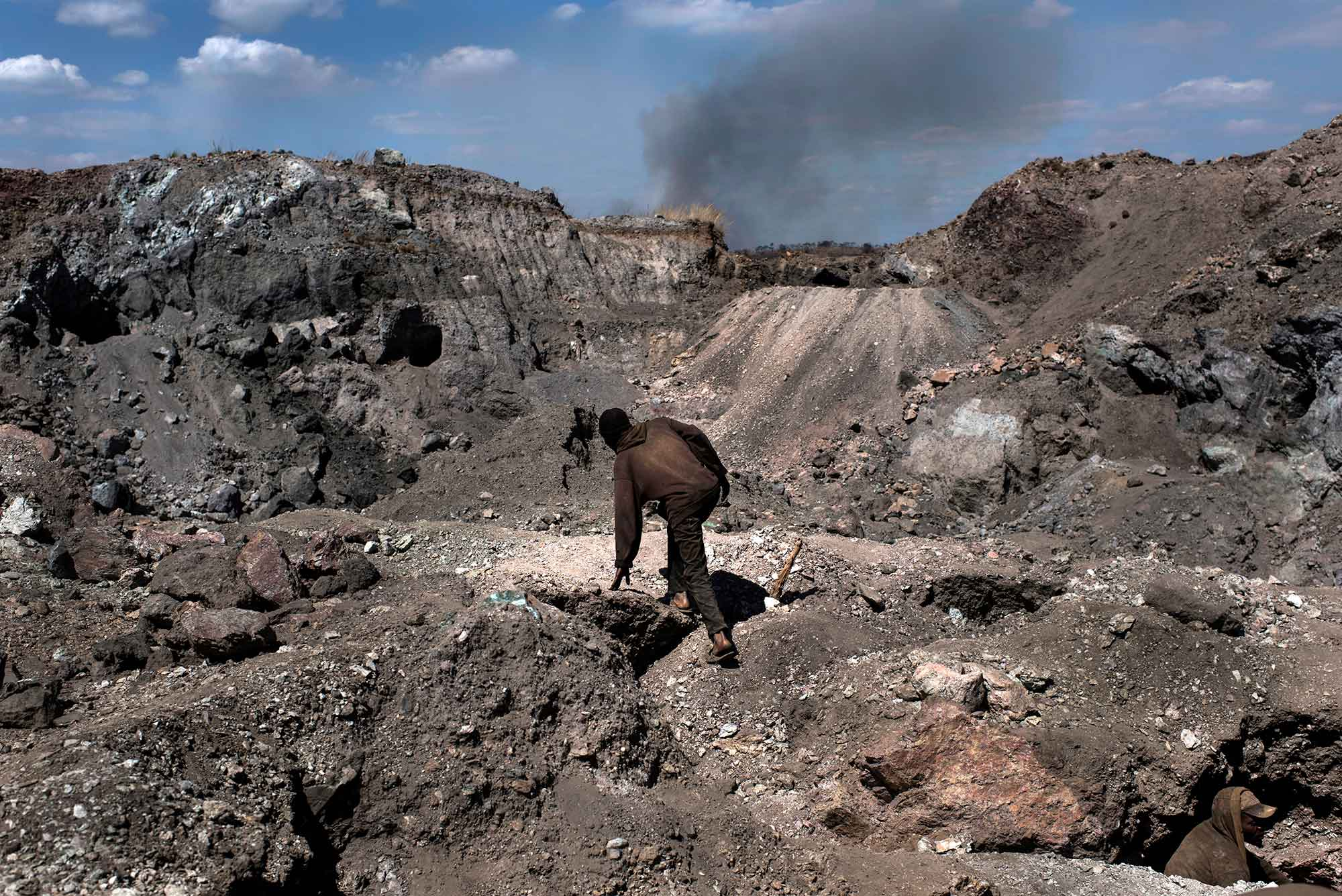 """KAWAMA, DEMOCRATIC REPUBLIC OF CONGO - JUNE 8 A """"creuseur,"""" or digger, climbs through the mine in Kawama, Democratic Republic of Congo on June 8, 2016. The cobalt that is extracted is sold to a Chinese company, CDM. Cobalt is used in the batteries for electric cars and mobile phones. Working conditions are dangerous with no safety equipment or structural support for the tunnels. The diggers are paid on average US$2-3/day. (Michael Robinson Chavez/The Washington Post)"""