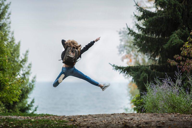 Frau mit Rucksack macht Luftsprung - omnia mea mecum porto