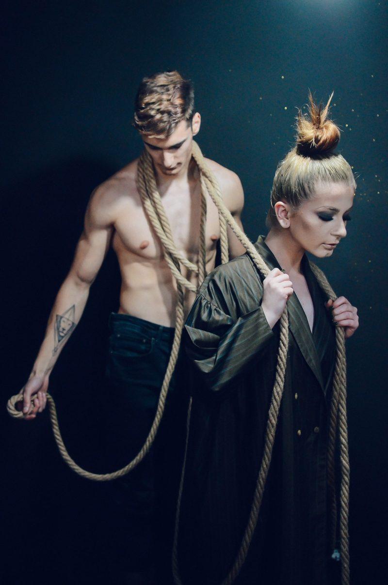 Frau zieht Mann an einem Seil hinter sich her