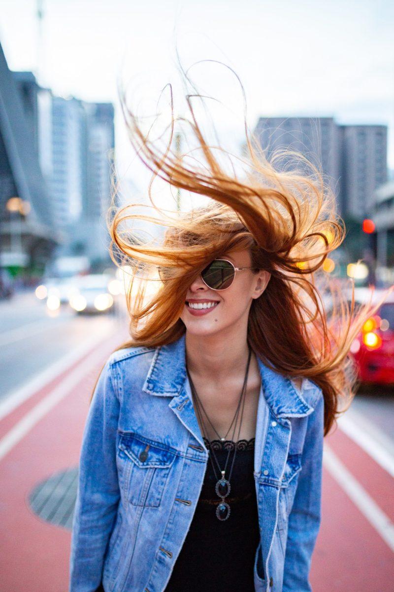 Frau steht auf der Straße mit wehendem Haar und lächelt