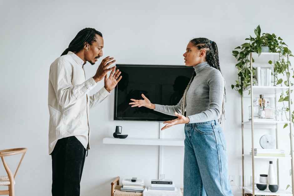 annoyed young ethnic couple quarreling in cozy apartment