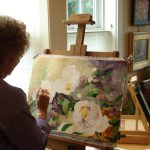 Sue Bennett works on a watercolor in her studio at Oregon Street Gallery