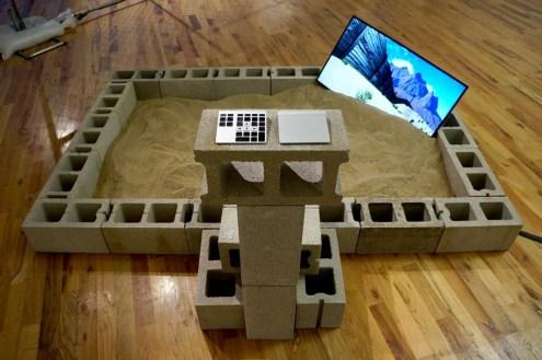 "Alfredo Salazar-Caro. ""Border Crossing Beta 2.0 aka Sonora aka el desaparecido,"" 2015 sand, cinder blocks, custom software, HD video monitor"