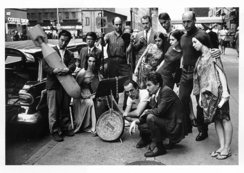 Peter Moore. Publicity photograph for 3rd Annual New York Avant Garde Festival, August 26, 1965. Left to right: Nam June Paik, Charlotte Moorman, Takehisa Kosugi, Gary Harris, Dick Higgins, Judith Kuemmerle, Kenneth King, Meredith Monk, Al Kurchin, Phoebe Neville. In front, kneeling, Philip Corner and James Tenney. Photograph © Barbara Moore/Licensed by VAGA, NY.