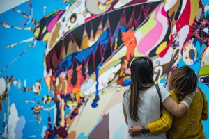 Two people with long hair look up at a bright and colorful mural. One person has their arm around the other.