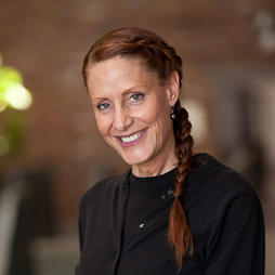 A woman with braided long red hair is smiling and looking at the camera. She is wearing a black shirt and sweater and a red brick wall is in the background.