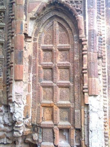 Articulation of a wooden false door in terracotta bricks and tiles