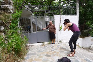 Mrs Maria agrees to be photographed in front of one of the houses where villagers were executed.