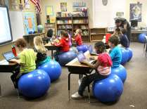 Audubon Park Elementary School third grade teacher Jeremy Cook (background right) teaches a math lesson in a 100% digital, book-free environment using a Smart Board, with his students using Dell netbooks, Wednesday, February 16, 2011. The students also use blue exercise balls to sit on, instead of traditional chairs. (Joe Burbank/Orlando Sentinel) Newsgate CCI-Id: B581070463Z.1 to go with leslie postal story for feb. 20