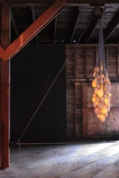 2014, slip-cast porcelain, light, hand knit and dyed cotton nets, steel pulley, trailer hitch, dimensions vary: ceiling height: 13', Installed at Loveland Feed and Grain, Loveland, CO