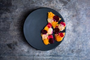 Black porcelain.Beets with onions on cracker.food by Dan Barber.photograph by Andrew Scrivani