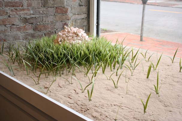 "2017 porcelain, paint, artificial grass, sand, 12""H (installation dimensions variable)"