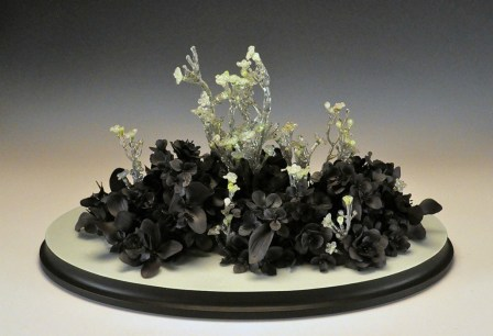 "hand formed black clay, resin, plastic flowers, wood, paint, 21"" x 13"" x 12"""