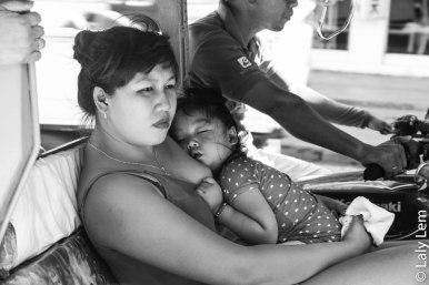 Dans un taxi tricycle, une mère et son enfant.