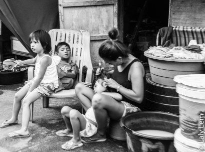 Une maman retire les poux sur la tête de son enfant, pendant que les autres attendent leur tour.