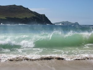Photo of crystal clear waters and big crashing blue waves on an Irish beach. The sun is shining and the cobwebs are being blown away.